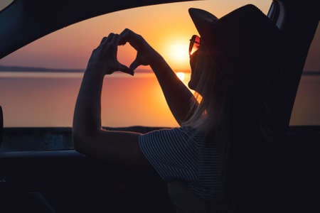 A young woman looks out the car window at the sunset on the sea. heart made with hands