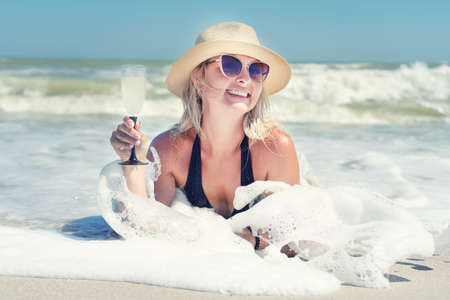Young sexy woman in a swimsuit and a straw hat drinks a glass of champagne on the seashore. 版權商用圖片