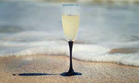 A glass of champagne by the sea.