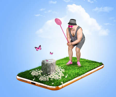 Cheerful man in a striped suit and hat catches butterfly in a butterfly net on a smartphone screen. Travel and vacation concept.Fun. 版權商用圖片