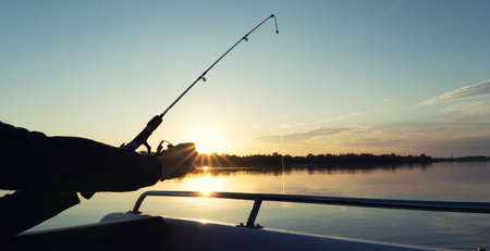 Fishing on the lake from a boat. Fishing rods in sunlight. Fishing rest concept.