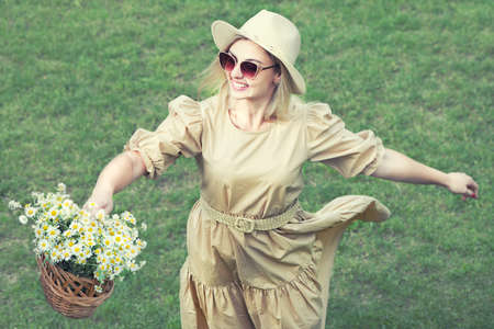 Beautiful woman in hat and with a basket of field daisies in sunny summer day. 版權商用圖片