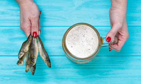 A woman holds a mug of cold beer and salted fish on a black wooden background.