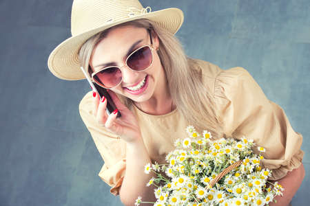 Beautiful woman in hat and with a basket of field daisies talking on a cell phone.