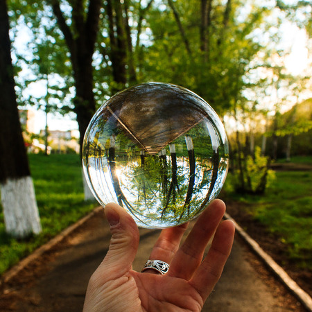 Arm holding the big transparent glass ball on the finger tips. Background is outdoor on the park road with green summer trees in sunset Stock Photo