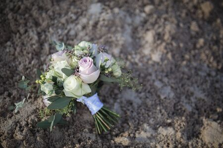 wedding bouquet with roses on the sand of industrial waste