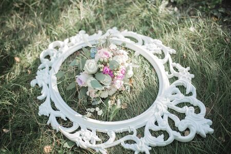 A wedding bouquet of roses in a frame on the grass