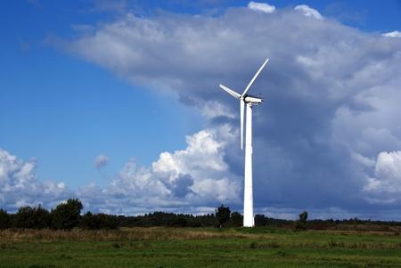 Windkraftanlage auf dem Hintergrund des blauen Himmels und der Wolken