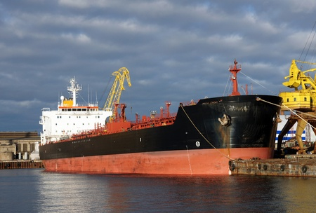 The tanker is moored in the port and loaded fuel photo