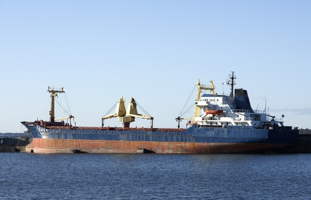 The cargoship costs in port on a background of the blue sky