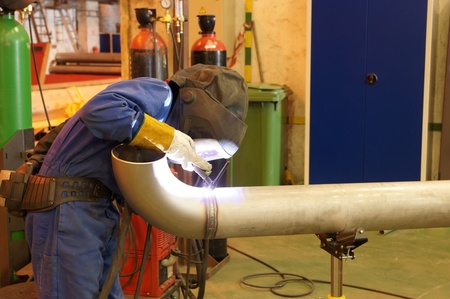 Factory worker welding  a metal pipe Stock Photo - 13358106