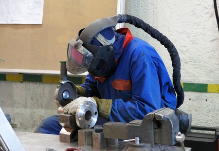 The worker in a protective mask cleans a pipe Stock Photo - 13358120