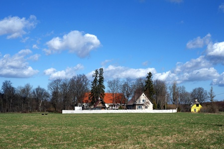 Country house on a background of the blue sky and clouds