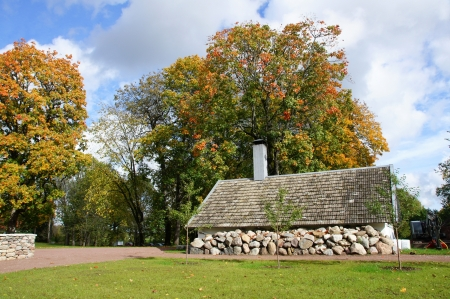 Old stone shed on a background of trees Stock Photo