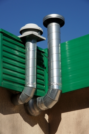 Pipes of ventilation are located on a wall of a building