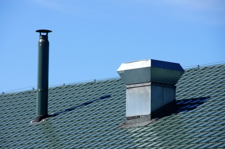 Pipe of ventilation are located on a roof of a  building