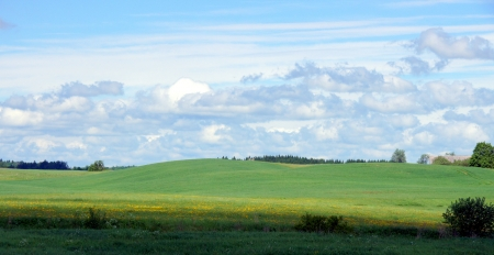 Meadow and clouds on a background of the sky