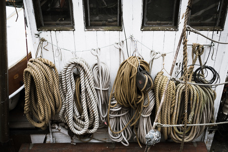 Ropes coiled, hanging on the front of a fishing boat wheelhouse. Stock Photo - 82670886