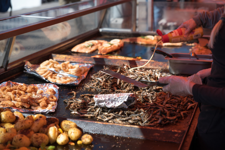 fish vendor: Grilling fish at Helsinki outdoor market.