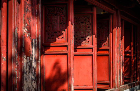Old red temple doors with ornate Asian carvings