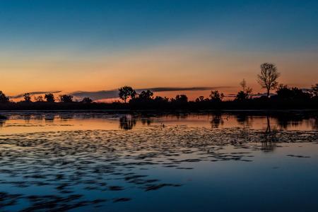 Sunset over the water on the Okavango Delta Botswana Stock Photo