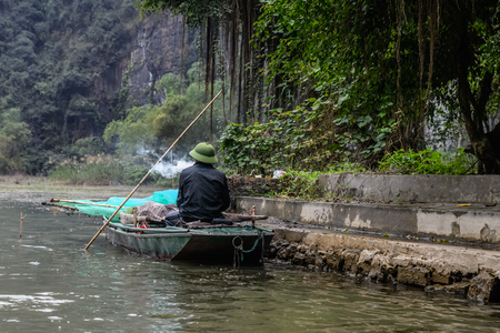 Fisherman smoking in his boat in Tam Coc Ninh Binh Vietnam