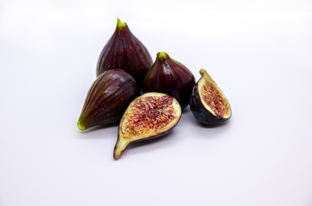 Ripe fresh figs against white backdrop