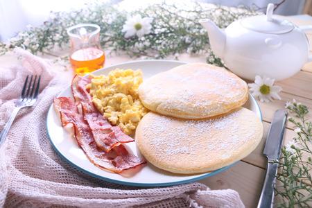 scrambled eggs: frescos panqueques con huevos revueltos y tocino para el desayuno.