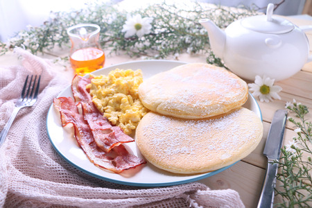 Fresh pancakes with scrambled eggs and bacon for breakfast. Stock Photo