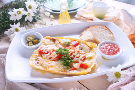 Vegetable omlette with grated cheese and chorizo served with bread, tomatoes, olive and jalapeno.