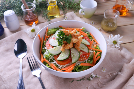Crispy sesame chicken salad with carrots, cucumbers, tomatoes and lettuce.