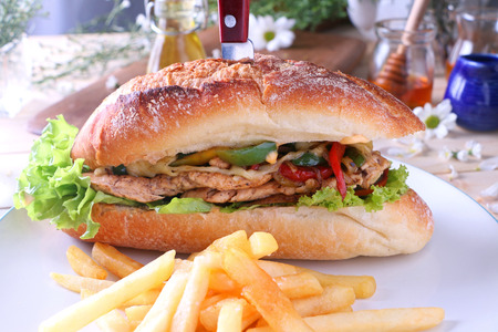 Roast chicken in fresh baguette closeup filled with onions, peppers morrarella cheese, served with french fries.