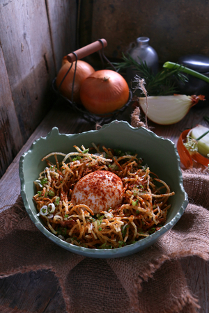 Gluton free fried noodles with bolied egg served in a cracked bowl.