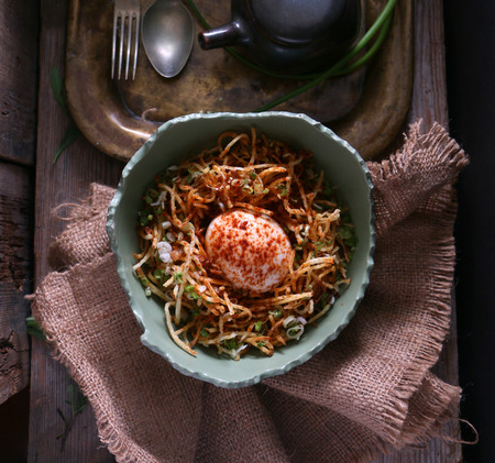 Gluten free fried noodles with boiled egg and onions served in a cracked bowl.