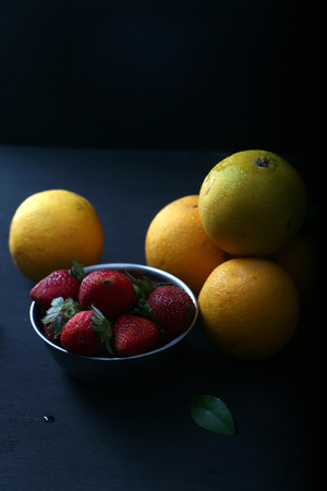Strawberries and oranges with moody, dark background. Stock Photo
