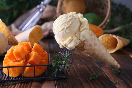 Mango ice cream and mango fruit on wooden table.