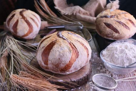 Fresh Artisan Sour Dough Bread on old kitchen table. Stock Photo