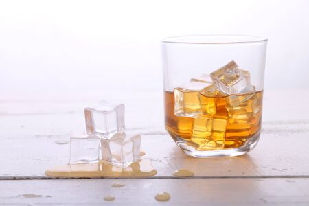 Single glass of whiskey with Ice cubes on white background