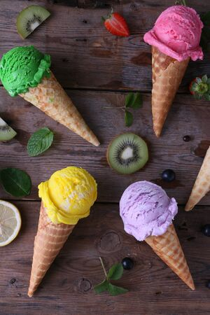 Variety of ice cream cones on wooden table.