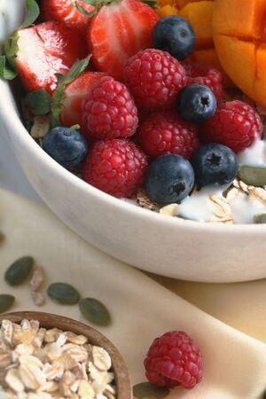Healthy gluten free fruit cereal with mango, strawberries, oats, yoghurt, blueberries, raspberries and pumpkin seeds