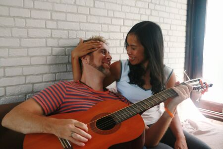 Mixed race couple, man playing guitar to asian girlfriend at home