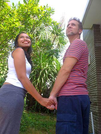 Happy mixed race couple holding hands in garden