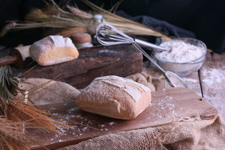 Small Pita bread lying on wooden board in kitchen Stock Photo