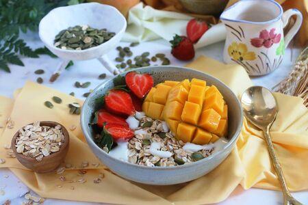 Healthy gluten free fruit cereal with mango, strawberries, oats, yogurt, blackcurrants, raspberries and pumpkin seeds Stock Photo