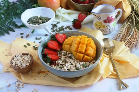Healthy gluten free fruit cereal with mango, strawberries, oats, blackcurrants, raspberries and pumpkin seeds Stock Photo