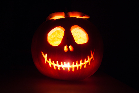 Scary Halloween pumpkin isolated on a black background. Scary glowing face trick or treat