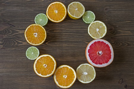 citrus fruits: round frame with citrus fruits on grey wooden background