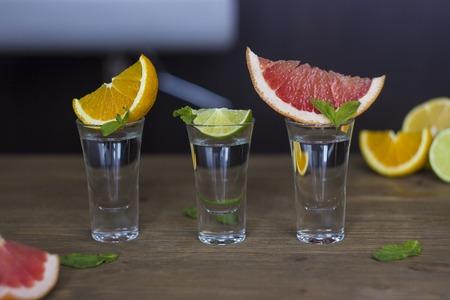 Shot drink set with diffrent citrus slices on bar background
