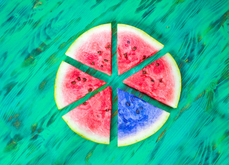 businness: Watermelon slices. A black sheep concept. Green wooden background. View from above
