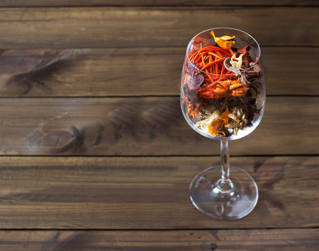 Autumn leaves in a wine glass on wooden table background. Seasonal, sunday relax and still life concept